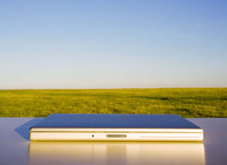 Laptop with grass and blue sky behind